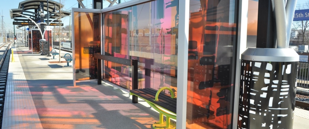 Sharon Dowell's glass windscreen with laminated black, pink, & orange patterns & human silhouettes as through a passing train window, cast colorful shadows on the 25th St Station light rail platform. Canopy columns with b&w metal abstract designs complement the windscreen.
