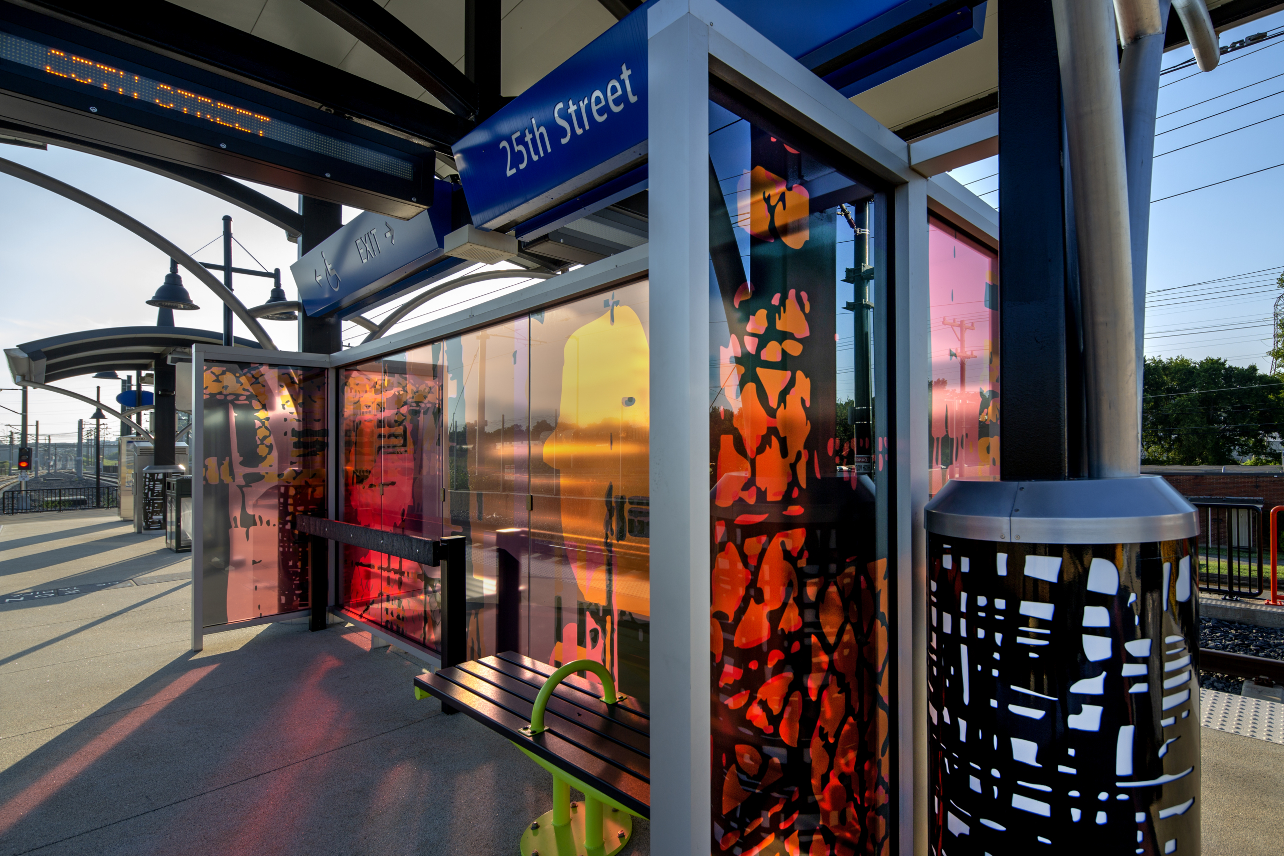 Glass windscreen with laminated black, pink, & orange patterns & human silhouettes as through a passing train window cast colorful shadows on the 25th St Station light rail platform. Canopy columns with b&w metal abstract designs complement the windscreen.