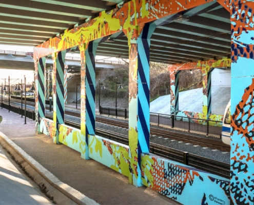 I-277 & 11th St underpass over light rail track & walkway in Charlotte. Painted in sky blue with cobalt blue & orange diagonal, repeating, lined patterns down sides of concrete support ballasts. Mesh-like & organic patterns in various bright colors throughout.