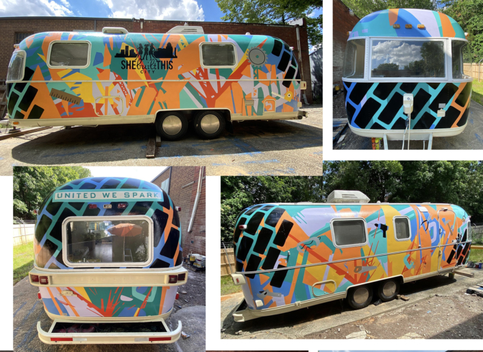 Aluminum Airstream Argosy completely painted in enamel, with images of tools on a brightly-colored background of geometric shapes. Large She Built This City logo in black on side. United We Spark in teal block letters over rear windshield.