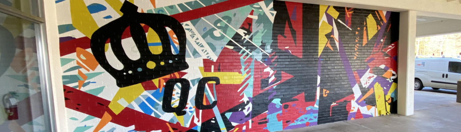 """Energetic mural of geometric shapes & abstracted trusses & beams in bold colors on brick wall. Charlotte NC's crown logo and """"QC"""" painted prominently in black on left side of mural. Located outside Bart's Bottle Shop, Eastway Shopping Center."""