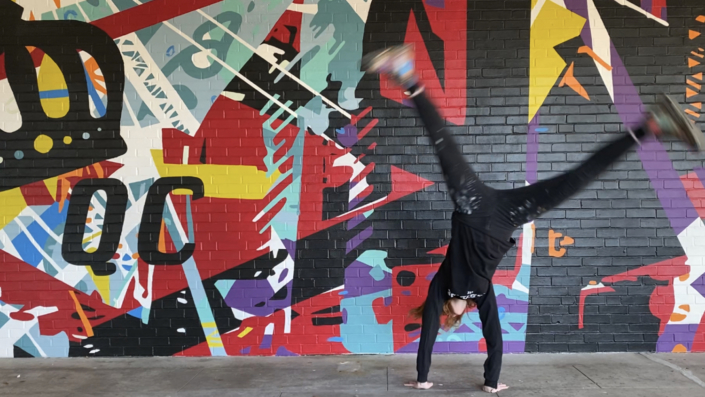 Figure in black clothing cartwheels in front of energetic mural of geometric shapes & abstracted trusses & beams in bold colors on brick wall. Charlotte NC's crown logo and QC painted prominently in black on left side of mural. Located outside Bart's Bottle Shop, Eastway Shopping Center.