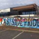 Detail of approx 950 sq ft mural covering multiple walls in Charlotte's Eastway Crossing mall parking area. Eastside Pride painted in thin, black block letters over a busy, colorful mural of abstract geometric shapes & lines.