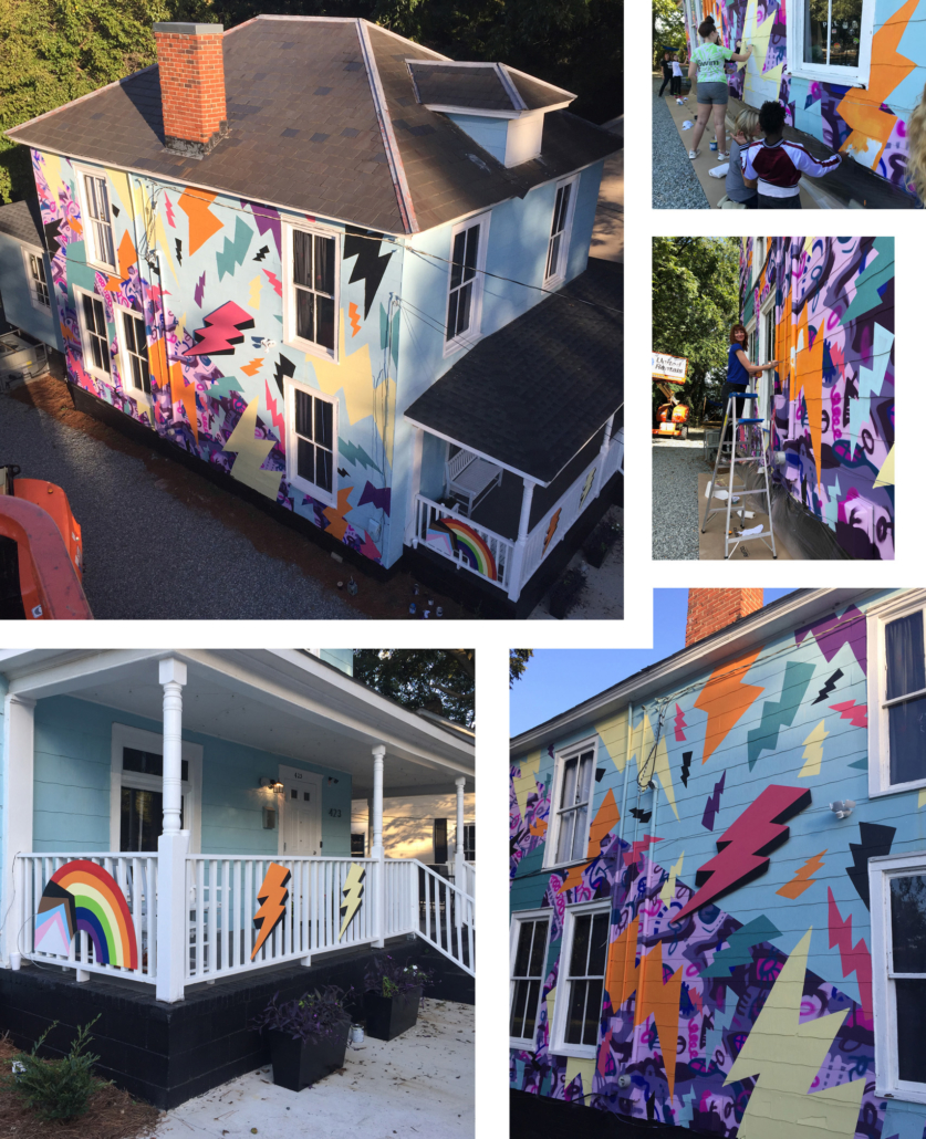 A colorful, two-story, hand-painted mural of comic book-style lightning bolts & playful shapes & lines covering the entire exterior wall of Girls Rock CLT headquarters. Summer camp volunteers and youth also helped create the inclusivity rainbow and painted, aluminum lighting bolt sculptures on front porch railing.