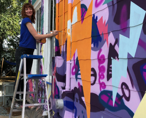 Sharon Dowell painting a colorful, two-story mural of comic book-style lightning bolts & playful shapes & lines covering the entire exterior wall of Girls Rock CLT headquarters.