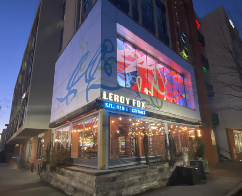 Corner view from street of 10' h x 50' w colorful, whimsical, abstract window film and building wrap over slow-changing, multi-colored LED lightbox. Above Leroy Fox in Charlotte's Southend. Collaboration with Christopher Hoslton for I Heart Rail Trail 2021.
